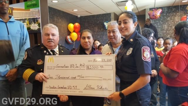 Chief Chornock and President Wahed accept a very large check from the owner of McDonald's.